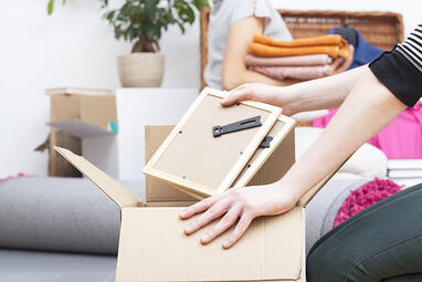 Close up of womans hand packing two photo frames